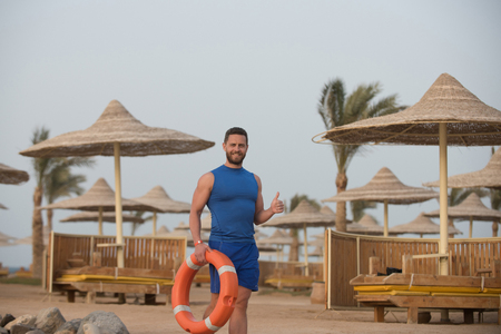 man with smiling happy bearded young face in blue sportswear shirt and short holding red life saver and showing thumb up on background of sun parasols sunbeds and palm at beach on summer vacations