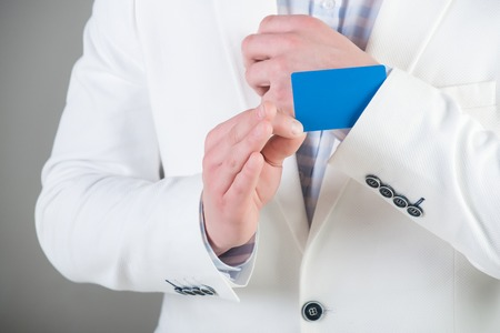 Businessman in white jacket on grey background. Empty business card in cuff. Ace up sleeve concept. Advantage and secret trump. Cheating and trick Reklamní fotografie