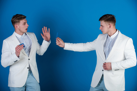 Men exchanging cards on blue background. Business communication and meeting. Businessmen wearing white jackets. Cooperation and partnership. Banking and saving concept.