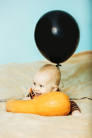 Halloween Kind mit glücklichem Gesicht. Baby in Bodysuit mit schwarzem Ballon. Party und traditionelles Essen. Feiertag und Feier. Kind mit orange Kürbis im Bett. Standard-Bild - 83468767