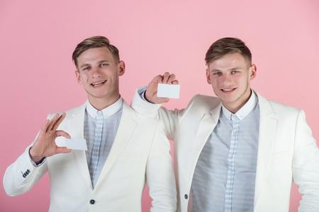 空白のカードと笑顔の男性はピンク色です。銀行とコンセプトを保存します。ビジネス コミュニケーションと会議。白のジャケットを身に着けてい