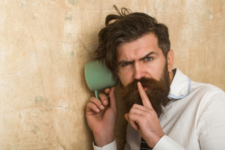 guy listen at wall. Man with beard hear gossip with cup. hipster with long hair. Beauty and fashion. neighbour and secret.