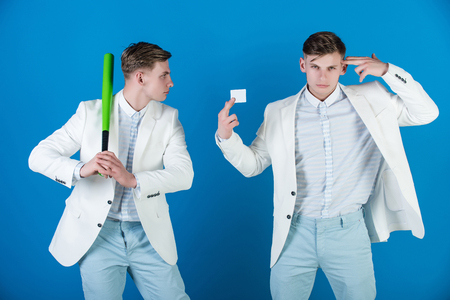 Business negotiations concept. Man showing finger gun with blank card. Businessman holding baseball bat on blue background. Managers wearing white jacket, shirt and pants. By force or persuasion. Stock Photo