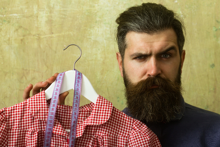 Man with beard hold dress and tape measure. Beauty and fashion. Shopping and black Friday. Tailor guy in workshop. Designer with measuring tape. Stock Photo