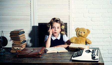 Child with briefcase and typewriter on table. Education and childhood. Little baby secretary in cabinet or library. Kid choose career of journalist or writer. Small girl with curler in hair read book. Zdjęcie Seryjne