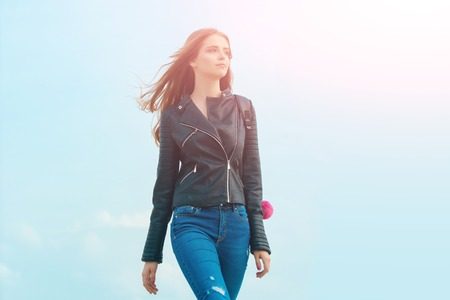 Woman with long hair. Girl in leather jacket. Beauty and fashion. Sexy woman outdoor. Fashion model on blue sky.