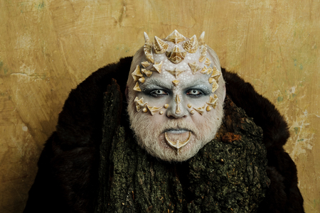 Druïde achter oude schors op beige muur. Kobold met hoorns op het hoofd. Man met drakenhuid en een bebaarde gezicht. Boomgeest en fantasieconcept. Monster met scherpe doornen en wratten.
