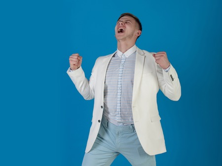 Business and success. Man shouting with winner gesture. Manager wearing white jacket, shirt and pants. Businessman celebrating achievement on blue background. Victory and reward concept.