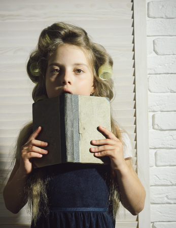 Small girl with curler in hair. Little baby with book. Child in school. Education and childhood.