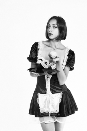woman holding apple and plate in hand dressed in beautiful sexy lace maid uniform posing, black and white