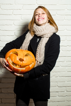 Halloween woman with happy face. Girl with orange scary pumpkin. Woman in coat and scarf at brick wall. Holiday and celebration. Party and traditional food.