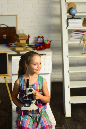 Girl with cheerful face expression in front of desk with school supplies, bookshelf and blackboard. Back to school concept. Schoolgirl holds microscope on study room background. Kid does experiments