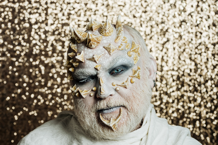 Wizard with white eyes. Monster with thorns on face. Demon with silver beard on golden bokeh background. Mystery and fantasy concept. Man with dragon skin. Stock Photo