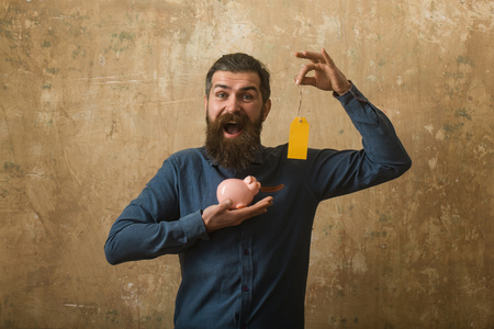 Loan and bankruptcy. Money and success. Businessman take bank credit. Man with beard on happy face. Guy hold shopping tag and moneybox. Stok Fotoğraf