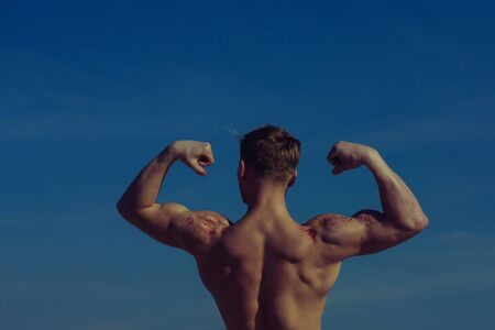Man with muscular wet body. Athletic bodybuilder pose as hercules. Gladiator or atlant. Sport and workout. Adam with glitter on bare chest.