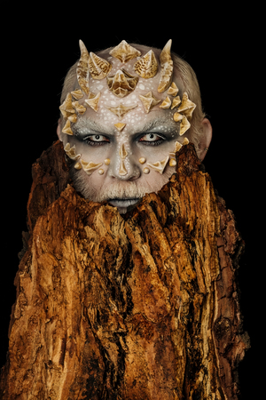Goblin with horns on head. Monster with sharp thorns and warts. Man with dragon skin and bearded face. Tree spirit and fantasy concept. Druid behind old bark isolated on black