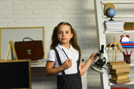 Kid does experiments. Schoolgirl holds microscope and pencil on light brick wall classroom background, defocused. Girl with shocked face near school supplies, shelf and board. Back to school concept