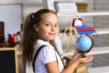 Kid studies geography. Girl with happy face expression near bookshelf with school supplies. Schoolgirl holds little globe on light brick wall classroom background, defocused. Back to school concept