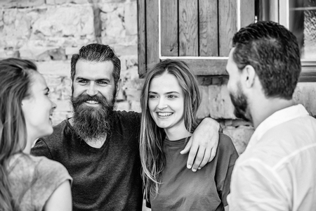 Couple of handsome bearded man with long beard and stylish hair and blonde pretty cute sexy woman or girl embracing and smiling to they friends on summer sunny day on stony wall background Banco de Imagens