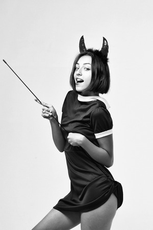 halloween woman or girl with smiling face in dress and devil horns or antlers holiday costume holds stick isolated on white background, black and white Stock Photo