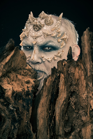 Tree spirit and fantasy concept. Monster with sharp thorns and warts. Druid behind old bark on black background. Man with dragon skin and bearded face. Goblin with horns on head. Stock Photo