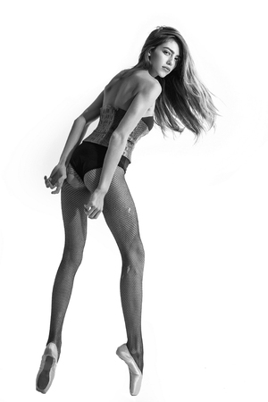 ballerina tights: ballerina with long hair and legs in pointe shoes and leather body suit, black and white Stock Photo