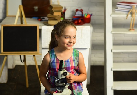Schoolgirl holds microscope on defocused study room background. Back to school concept. Kid does experiments. Girl with happy face in front of desk with school supplies, bookshelf and blackboard
