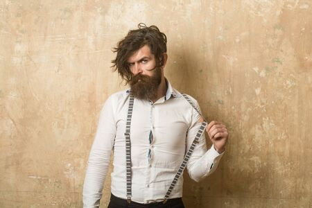 barbershop: Business fashion and beauty. Fashion model with stylish hair. Guy or businessman at textured wall. Man with long beard and mustache on face. Hipster in shirt and suspenders.