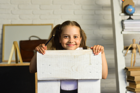 Schoolgirl sits on white chair, on defocused study room background. Back to school concept. Girl with happy face in front of school supplies. Kid holding dark pencil gets ready for school Stock Photo