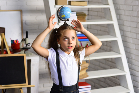 Kid does experiments. Schoolgirl holds globe on head on light classroom background, defocused. Back to school concept. Girl with concentrated face near shelf with school supplies and blackboard Stok Fotoğraf