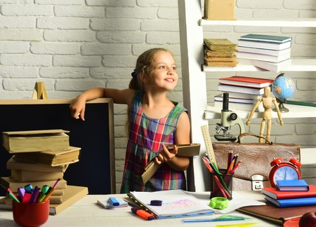 Kid with colorful stationery on white wall background. Childhood and back to school concept. Pupil with books and school supplies. Girl with happy face does homework.