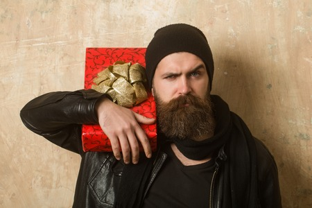 Christmas and birthday. Hipster with present box in hat. Guy with serious face and gift pack. Man with long beard. Holiday celebration and shopping.
