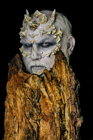 Monster with sharp thorns and warts. Druid behind old bark on black background. Tree spirit and fantasy concept. Man with dragon skin and bearded face. Goblin with horns on head. Stock Photo