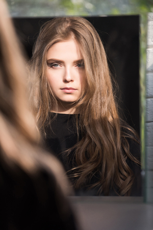 Woman with long hair and pretty face. Girl look at mirror. Hairdresser and barber. Beauty and fashion. Skincare and salon.