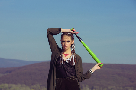 Sport or criminal girl outdoor. Beauty and fashion. Hooligan on blue sky. Bandit gang and conflict. Woman with baseball bat. Reklamní fotografie - 83849931