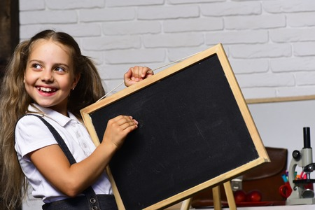 Schoolgirl with happy smile holds small blackboard. Girl in her classroom or laboratory with bag and stationery. Kid and school supplies on white brick background. Back to school and childhood concept