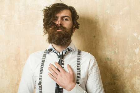 barbershop: Business fashion and beauty. Guy or businessman at textured wall. Man with long beard and mustache on face. Fashion model with stylish hair. Hipster in shirt and suspenders with musical tie. Stock Photo