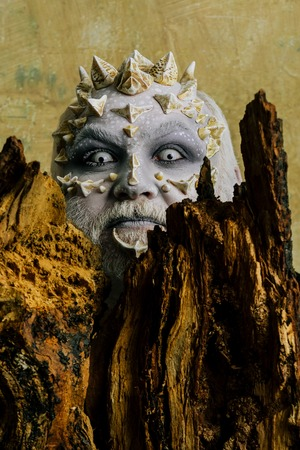 Druid behind old bark on beige wall. Tree spirit and fantasy concept. Goblin with horns on head. Man with dragon skin and bearded face. Monster with sharp thorns and warts.