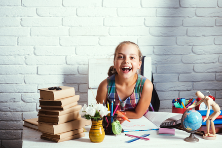 Back to school concept. Schoolgirl with smiling face draws in art book. Girl with books, globe and colorful stationery on desk. Kid near pile of textbooks and school supplies on white brick background