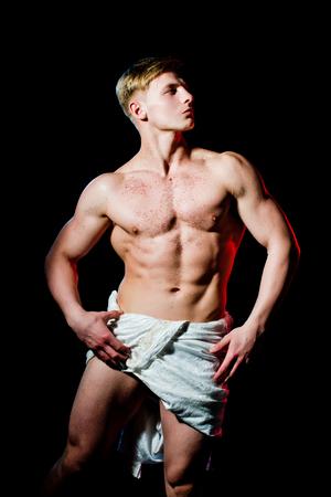 운동 보디 빌딩으로 동상으로 포즈. 운동과 운동. 검투사 또는 그리스 신. 흰색 근막에 근육질의 젖은 몸매를 가진 남자. 벌거 벗은 가슴에 반짝이는 아