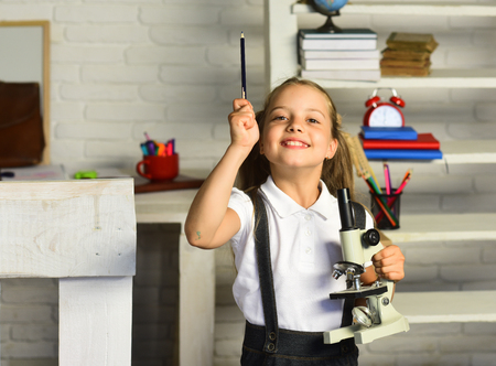 Schoolgirl holds microscope and pencil on light classroom background, defocused. Back to school concept. Girl with happy face in front of desk with school supplies, bookshelf. Kid does experiment Stok Fotoğraf