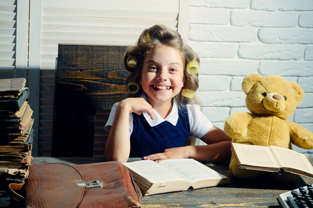 Little baby secretary in cabinet with bear. Kid choose career of journalist or writer. Education and childhood. Small girl with curler in hair read book. Child with briefcase and typewriter on table.