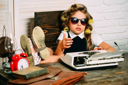 Little baby secretary. Kid choose career in glasses. Small girl with curler in hair. Education and childhood. Child with briefcase and alarm clock.