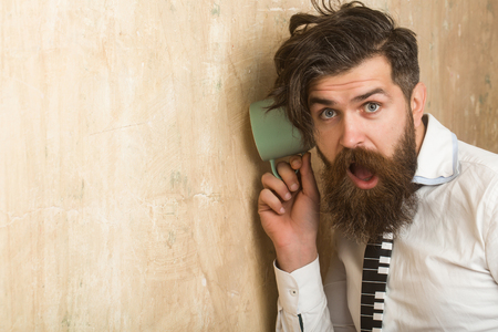 Man with beard hear gossip with cup. guy listen at wall. Beauty and fashion. hipster with long hair. neighbour and secret, copy space