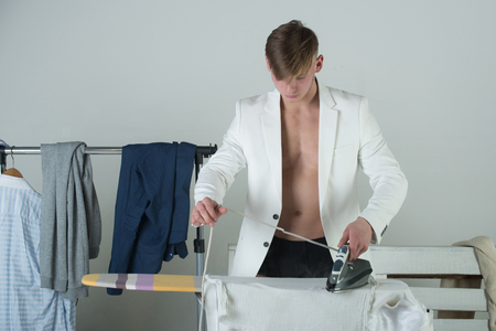 Athlete with muscular torso and chest. Clothes hanging on rack on grey background. Housework and fashion concept. Man ironing shirt with iron. Macho wearing white jacket.