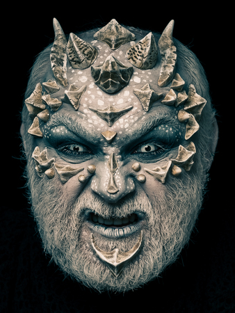 creepy alien: Alien or reptilian makeup with sharp thorns and warts. Man with dragon skin and beard. Demon head isolated on black. Monster face with evil look of white eyes. Horror and fantasy concept.