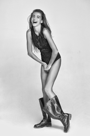 model or smiling woman with long wet hair in bodysuit and dirty boot, black and white