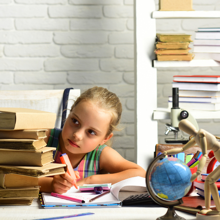 Schoolgirl with serious face draws in album and looks at pile of books. Back to school concept. Girl with globe and colorful stationery on desk. Kid near and school supplies on white brick background Stock Photo