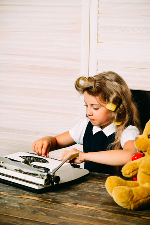 Education and childhood. Little baby secretary with bear. Small girl with curler in hair with typewriter. Kid choose career of journalist or writer. 版權商用圖片