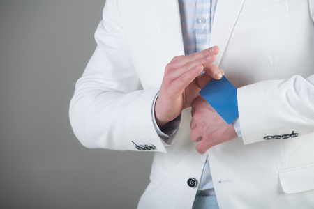 Ace up sleeve concept. Empty business card in cuff. Businessman in white jacket on grey background. Advantage and secret trump. Cheating and trick